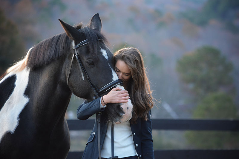 Claire McCown petting her horse