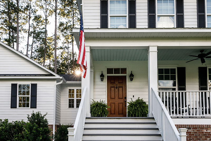 Front Porch with Stairs of All American White Farmhouse with Woods
