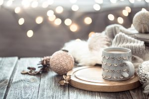 Coffee cup over Christmas lights bokeh in home on wooden table with sweater on a background and decorations. Winter mood, holiday decoration, magic Christmas.